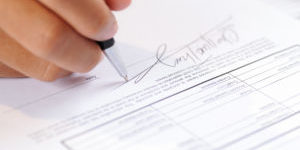 Closeup of person signing document with ball pen. Contract lying on table. Agreement concept. Cropped view.